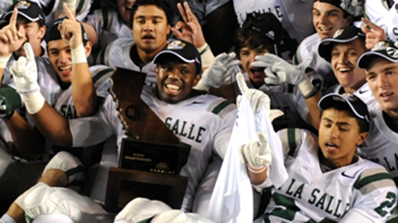 De La Salle senior Michael Hutchings has the CIF Open Division state title trophy in his lap as he and his teammates celebrate after they beat Centennial of Corona 48-28 on Saturday night. Photo by Scott Kurtz.