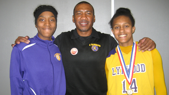 Veteran head coach Ellis Barfield of Lynwood is flanked by seniors Amber Blockmon and Alize Lofton after the Knights won the 2013 CIF Southern California Division II title last Saturday. Photo: Ronnie Flores.